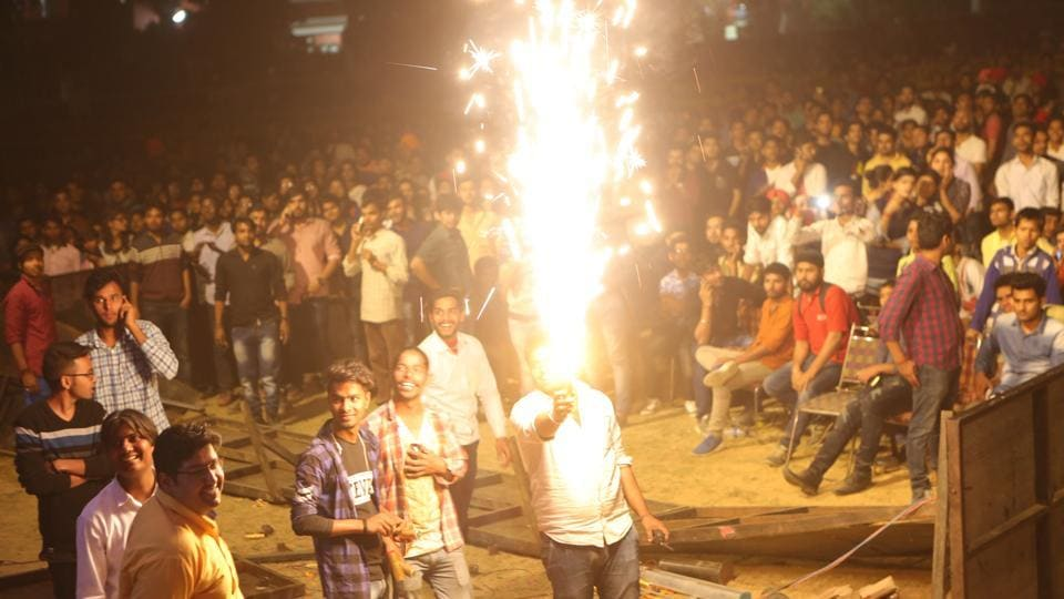 A student at the venue holds a firework in his hand. Many students were seen pushing each other and causing disruption in the concert. (Manoj Verma/HT Photo)