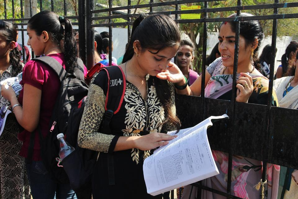 A student does a last-minute brush up while her family member wishes her luck outside an exam centre in Thane.