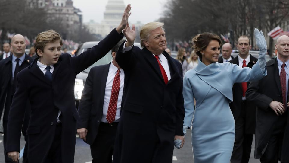 President Donald Trump waves as he walks with first lady Melania Trump and their son Barron during the inauguration parade on Pennsylvania Avenue in Washington.