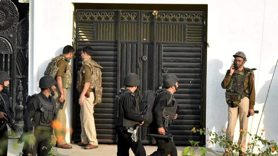 Uttar Pradesh anti-terror squad members take position near a building where the suspected terrorist was holed up in Thakurganj area of Lucknow on Tuesday.