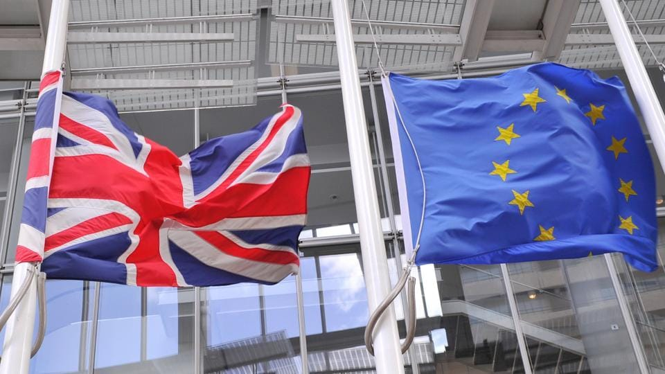 The British Union flag (left) and the European Union flag (right) fly in London on March 2, 2017.