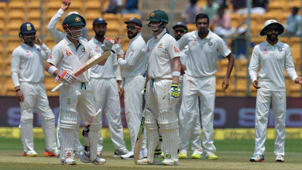 Australian captain Steve Smith (centre), vice captain David Warner, and the Indian team wait for the third umpire's decision on Warner's appeal for a review on his LBW dismissal on Day 4 of the second India vs Australia Test in Bangalore on Tuesday.