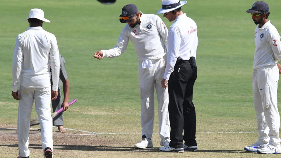 India captain Virat Kohli points out crumbled parts of the pitch to umpire Richard Kettleborough during the Pune Test last month.