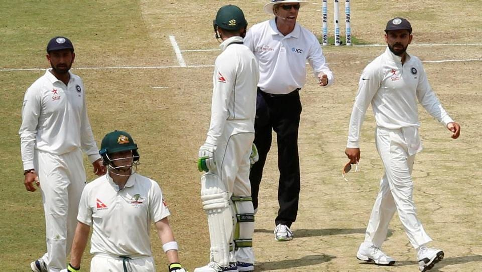Virat Kohli (R) speaks to the umpire as Steven Smith (2nd L) walks off the ground after being dismissed during second India vs Australia Test.