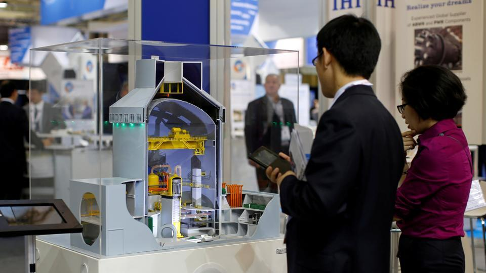 Visitors look at a nuclear power plant station model by American company Westinghouse at the World Nuclear Exhibition 2014, the trade fair event for the global nuclear energy sector, in Le Bourget, near Paris October 14, 2014.