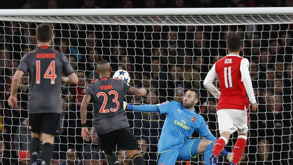 FC Bayern Munich's Chilean midfielder Arturo Vidal ( 2nd left) scores their fourth goal past Arsenal FC 's Colombian goalkeeper David Ospina during their UEFA Champions League last 16 second-leg match at The Emirates Stadium in London on Tuesday.