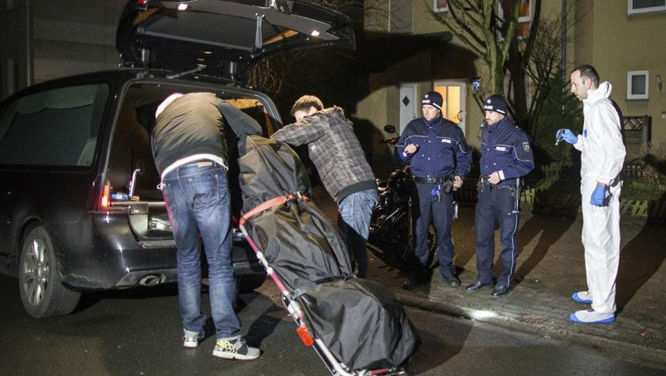 Undertakers lift a stretcher with a bodybag into a hearse in Herne, Germany.