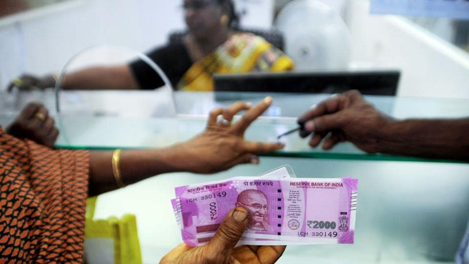 A November 17, 2016, photo shows a woman holding Rs 2000 notes as she has her finger marked with indelible ink after exchanging old 500 and 1000 notes at a bank in Chennai.