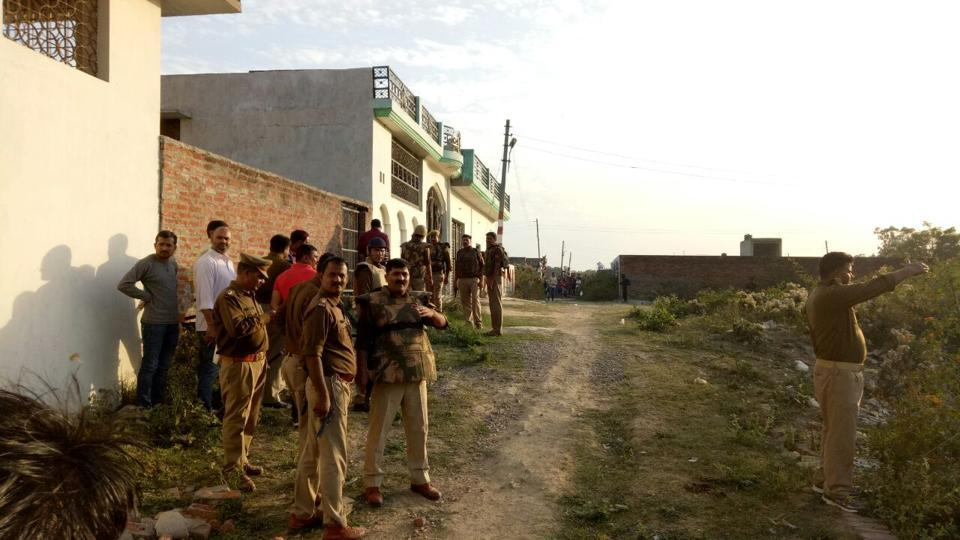 Policemen gather near a building where a suspected militant was holed up in Lucknow on Tuesday. (Deepak gupta/ht photo)
