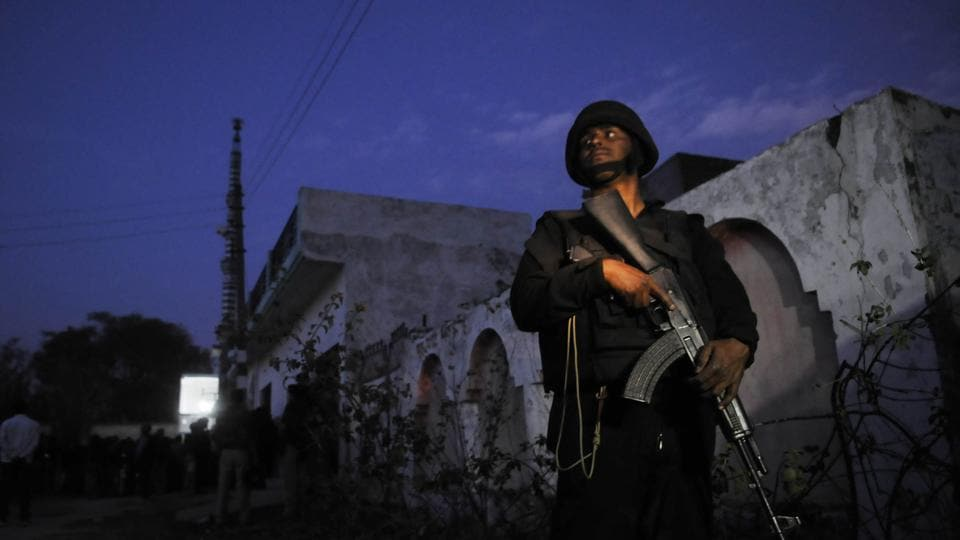 Cops stand guard near the house where a suspected militant was holed up, in Lucknow.