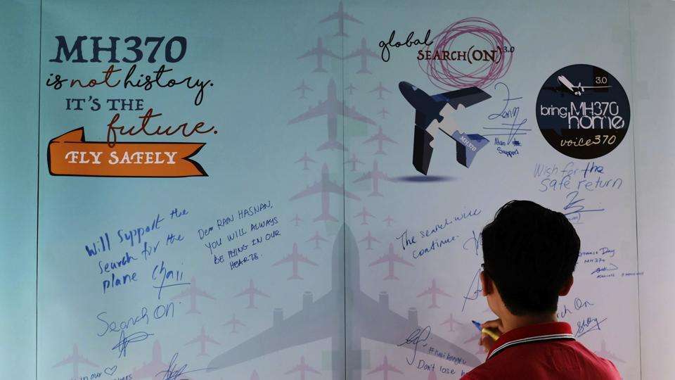 A man writes a condolence message during the Day of Remembrance for MH370 event in Kuala Lumpur, Malaysia.