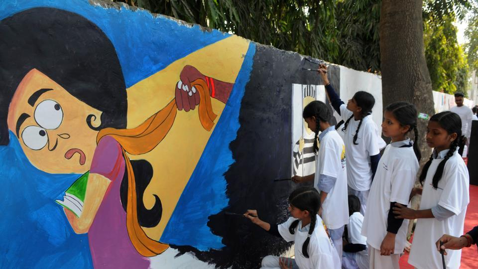 Students of Senior Secondary School, Khandsa, paint a graffiti on the wall outside Gurgaon police commissioner's office on International Women's Day on Wednesday.