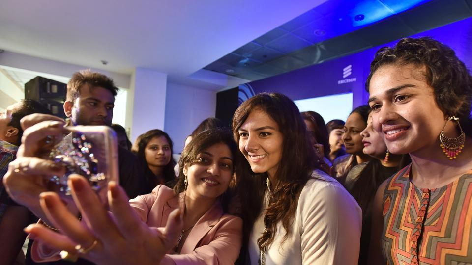 Women click selfies with Geeta Phogat (centre) and Babita Phogat (right) at a function held onWomen's Day.