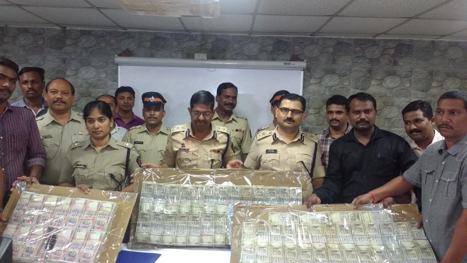 Police officers display the old notes.