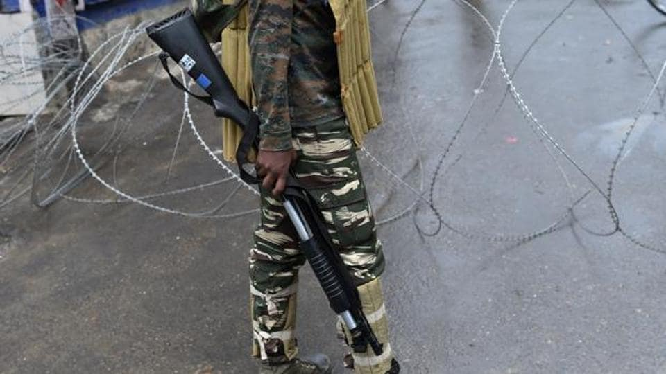 A paramilitary trooper holds a pellet gun as he stands guard during a curfew in Srinagar.