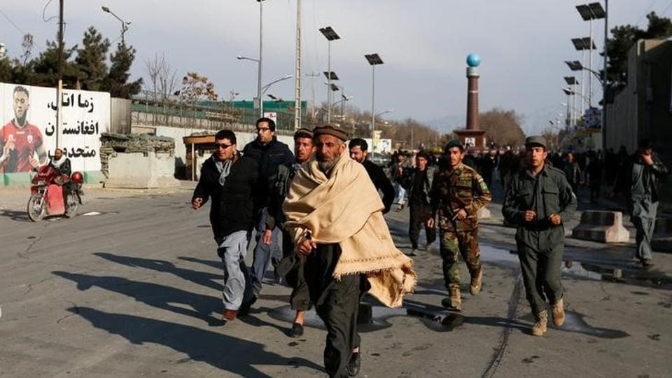 Afghan men walk toward a military hospital in Kabul that was attacked by the Islamic State to see their relatives  on March 8, 2017.