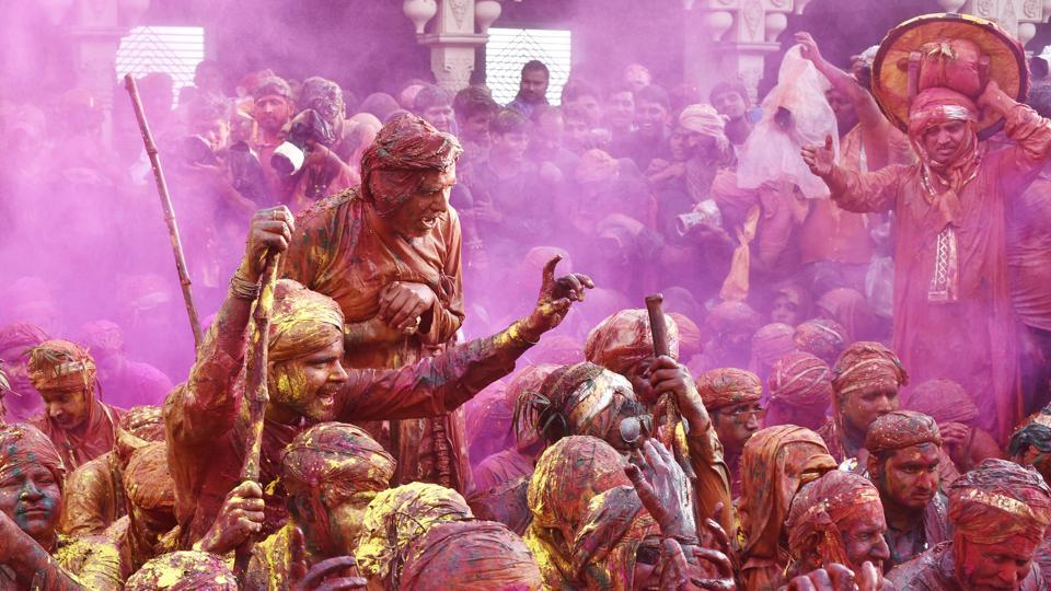 Indian villagers smear themselves with colour during the Lathmar Holi festival in Nandgaon, around 120 kms from New Delhi. The women of Nandgaon chase the men from Barsana, the legendary hometown of Radha, consort of Hindu God Krishna, with wooden sticks in response to the latter's efforts to put colour on them.