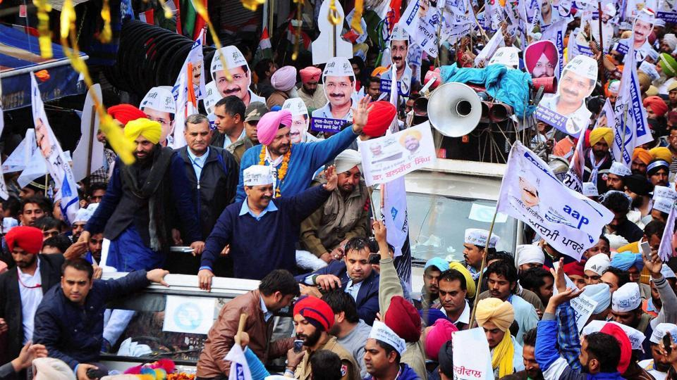 Arvind Kejriwal with party MP Bhagwant Mann and AAP MLA candidate in Patiala, Balbir Singh wave to their supporters during a road show in Patiala. (PTI)