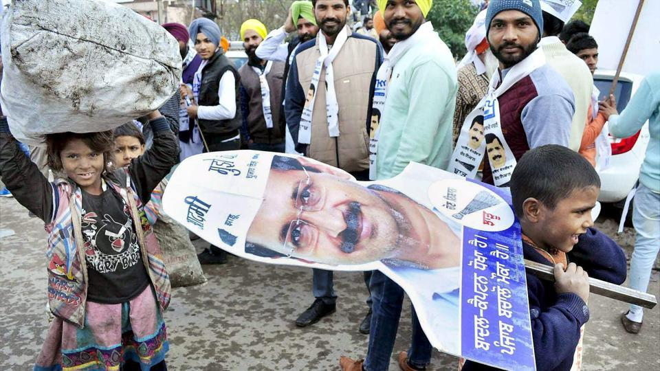 Children hold a cut-out of Delhi Chief Minister Arvind Kejriwal during an election road show in Patiala on 27th January 2017. (PTI)