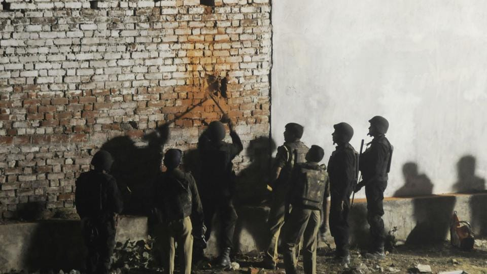 Uttar Pradesh anti-terror squad members make hole in the wall of the house where Saifullah, a terror suspect, was hiding in the Thakurganj area of Lucknow on Tuesday.