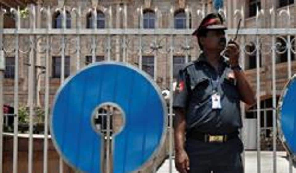 A security personnel stands guard in front of the gate of the State Bank of India (SBI) regional office in Kolkata.