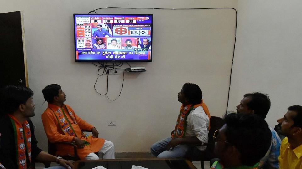 BJP workers watching the exit poll results on TV at party the office in Lucknow on March 9.