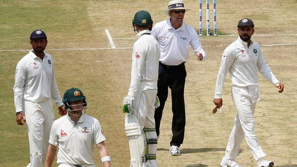 India's captain Virat Kohli (right) speaks to the umpire as Australia's captain Steven Smith (2nd L) walks off the ground after being dismissed.