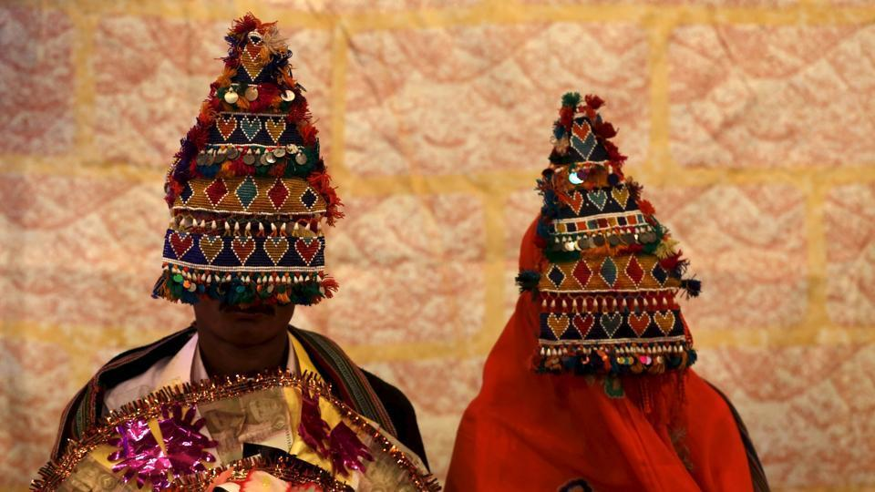 File photo of a Pakistani Hindu bride and groom wearing traditional handmade garlands waiting for their wedding to start during a mass marriage ceremony in Karachi in January 2016.