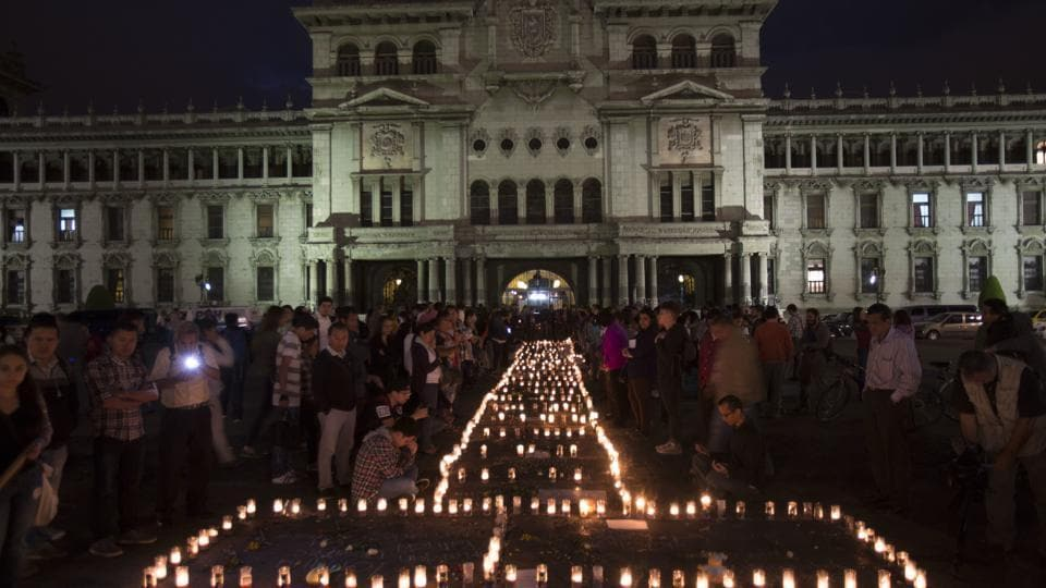 People hold a candlelight vigil outside the National Palace in remembrance of the girls who died in a fire at the Virgin of the Assumption Safe Home in Guatemala City.