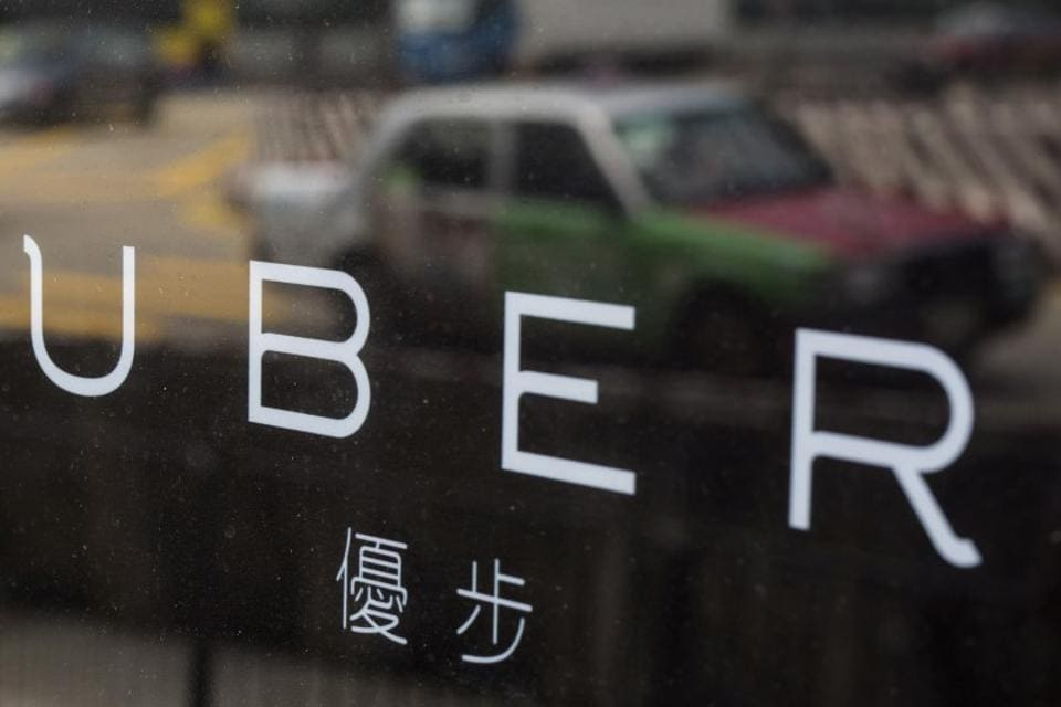 A taxi is reflected in a window at the office of taxi-hailing service Uber Inc in Hong Kong, China