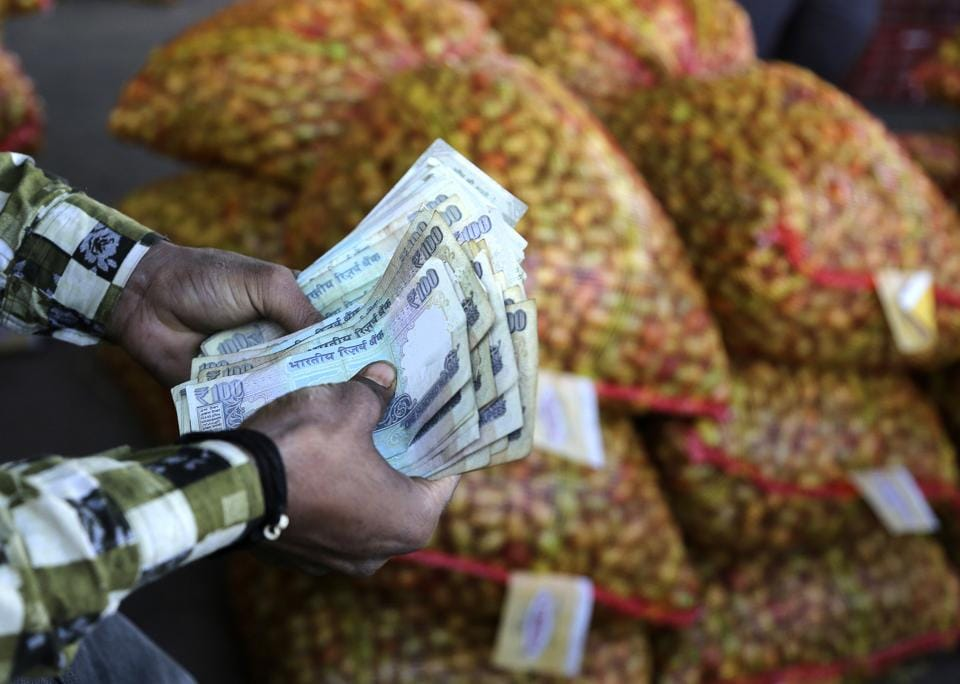 An Indian trader counts rupees at wholesale vegetables market on the outskirts of Jammu, India, Monday, March 6, 2017. India's economy registers a faster-than-expected growth of 7 per cent in fiscal third quarter 2016-17, notwithstanding the demonetization of high-value banknotes in November that caused immense hardship to small businesses dependent on cash transactions. (AP Photo/Channi Anand)