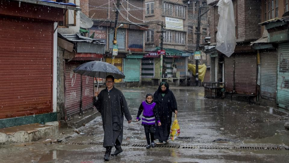 A Kashmiri family walk past shuttered shops as it snows during a strike in Srinagar on Friday.