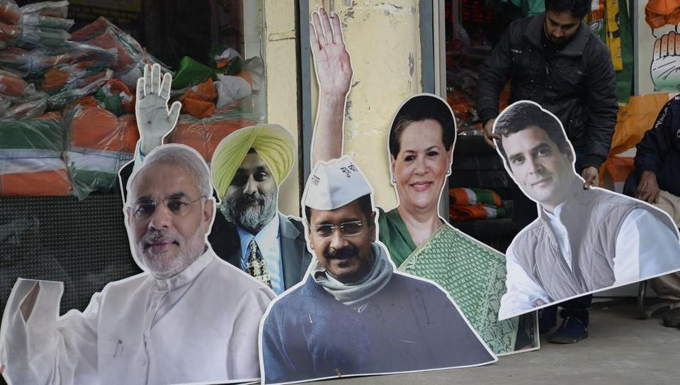 A shopkeeper adjusts cardboard cut-outs of political parties leaders (L-R) Prime Minister Narender Modi, Punjab Deputy Chief Minister Sukhbir Singh Badal, Aam Admi Party chief Arvind Kejriwal, Congress President Sonia Gandhi and Congress Vice President Rahul Gandhi for sale in Jalandhar on January 20, 2017.