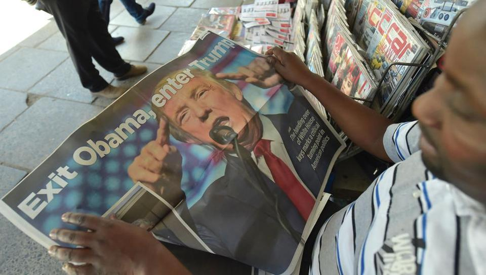 A man reads a newspaper pullout depicting USPresident Donald Trump. The president himself reads a a stack of newspapers — including The New York Times, The Wall Street Journal, The Financial Times, The Washington Post and The New York Post.