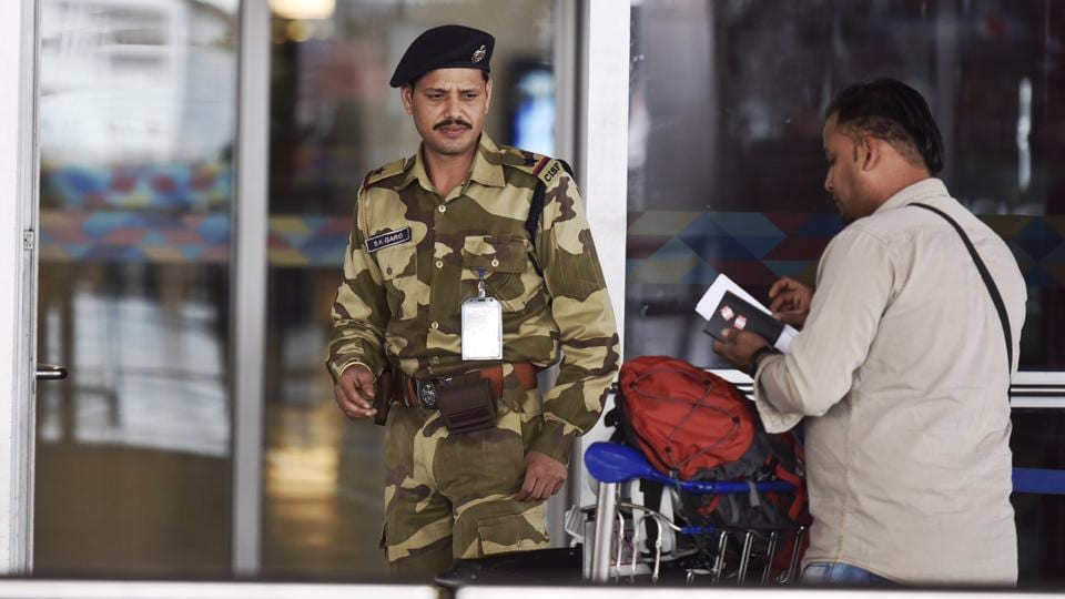 A CISF security personnel stops a passenger for security check at the IGI Airport in New Delhi.