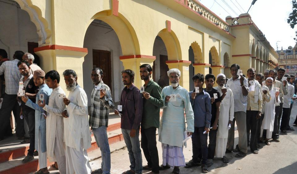 People wait in queue to caste their vote for Assembly elections, in Varanasi.