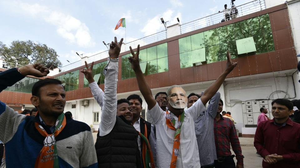 BJP workers celebrate outside their office in Lucknow after elections results showed leading in Uttar Pradesh.