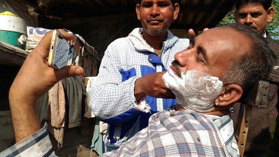 A man watching the election results on his mobile phone as he gets a shave outside a counting centre in Fazilka on Saturday.  (Anil Dayal/HT)