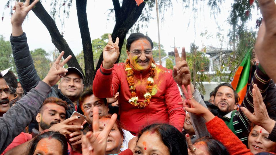 Senor BJP leader Ramesh Pokhariyal Nishank celebrates with party workers after the declaration of assembly election results in Dehradun on Saturday.