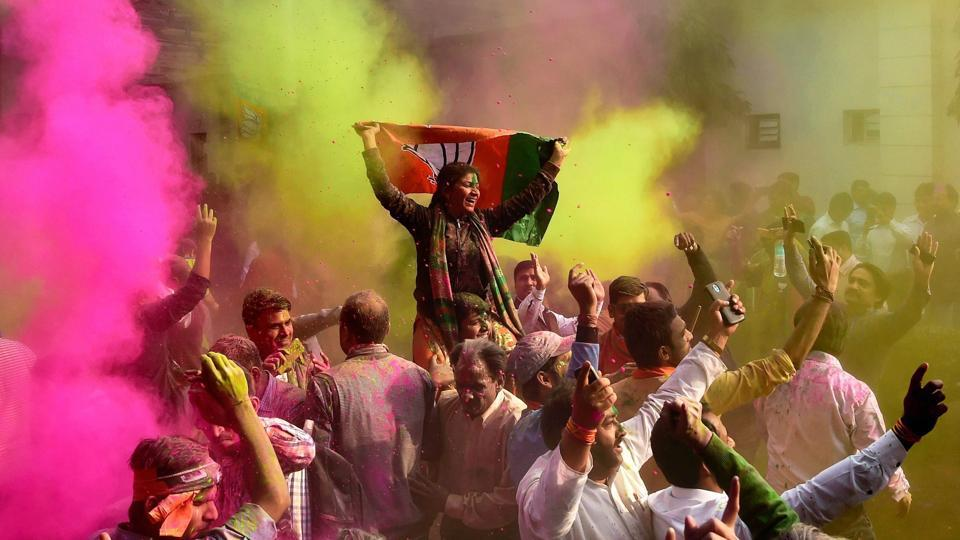 BJP workers celebrate the party's victory in the UP and Uttarakhand Assembly elections, at the party headquarters in New Delhi on Saturday.