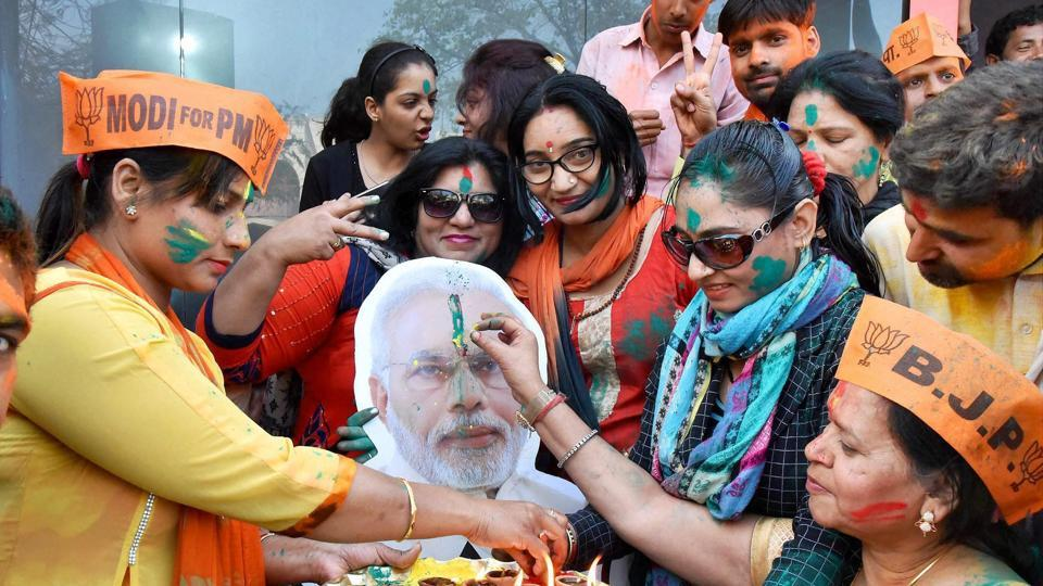 BJP workers celebrate the party's win in the assembly elections in Prime Minister Narendra Modi's Lok Sabha constituency, Varanasi, on Saturday.