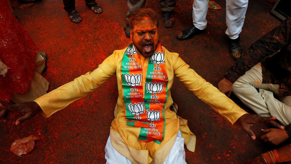 A supporter of the Bharatiya Janata Party (BJP) celebrates after learning of the initial poll results outside the party headquarters in Kolkata, India. (Rupak De Chowdhuri / REUTERS)