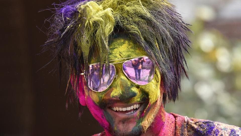 A man face covered with bright neon powder poses for a picture during Holi celebration.  (Virendra Singh Gosain/HT PHOTO)