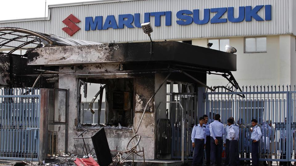 Security guards stand near a burnt down reception block of Maruti Suzuki factory in Manesar, near New Delhi, in July 2012.