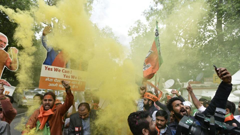 BJP supporters declare an early Holi as early trends are favouring them, at the party headquarters in New Delhi. (Mohd. Zakir/HT Photo)