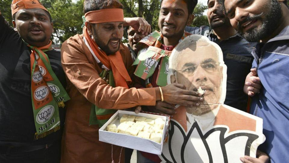 BJP supporters share sweets  at the party headquarters in New Delhi (Mohd. Zakir/HT Photo)