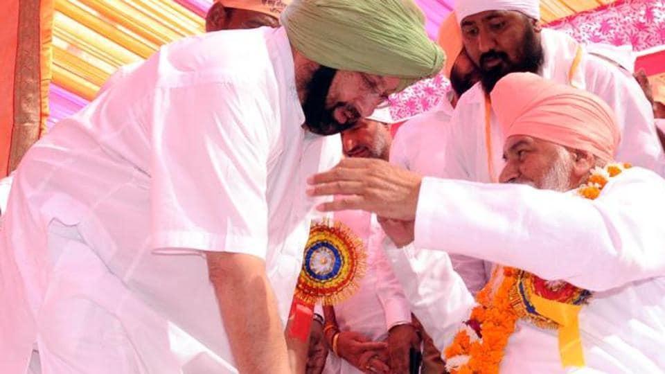 In this file picture Congress leader  Capt Amarinder Singh is seen seeking blessings of Sant Nirajan Das, head of Dera Ballan, during a function in Patiala