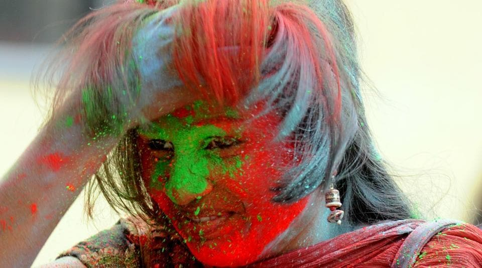 A girl with her  face smeared with  red colour powder at college campus in Ranchi. (Parwaz Khan / HT Photo)