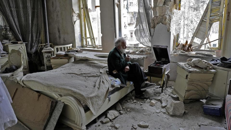 Mohammad Mohiedine Anis, 70, smokes his pipe as he sits in his destroyed bedroom listening to music on his vinyl player in Aleppo's formerly rebel-held al-Shaar neighbourhood. (JOSEPH EID / AFP)