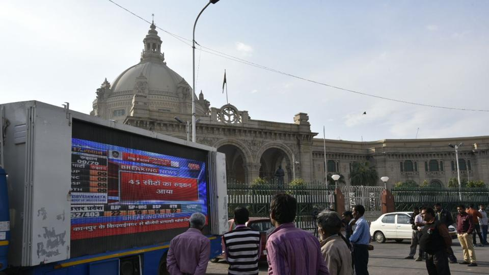 People look on at a screen projecting state election results in front of  the Vidhan Sabha in Lucknow , India on Tuesday, March 11, 2017. Early trends indicate a BJP lead in Uttar Pradesh. (ARVIND YADAV/HT PHOTO)